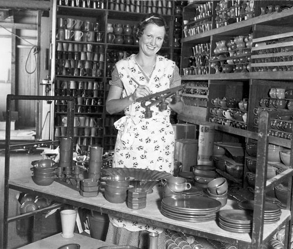 Woman marking pottery in a storage room containing numerous completed pottery items, c. 1930