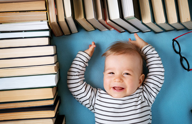 baby laying down surrounded with books