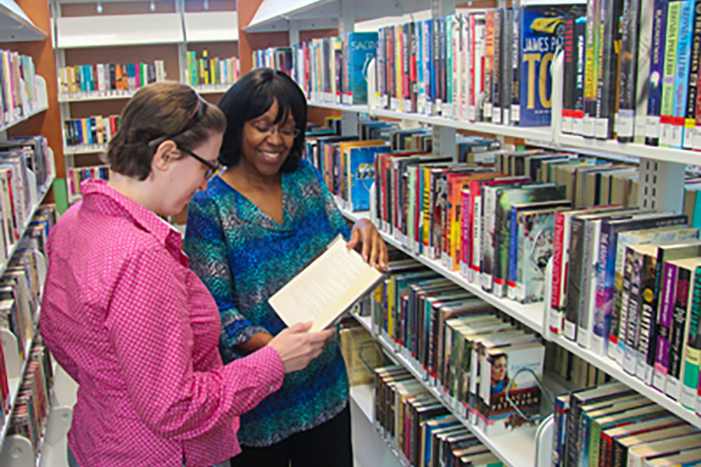 Librarian helping a woman find a book