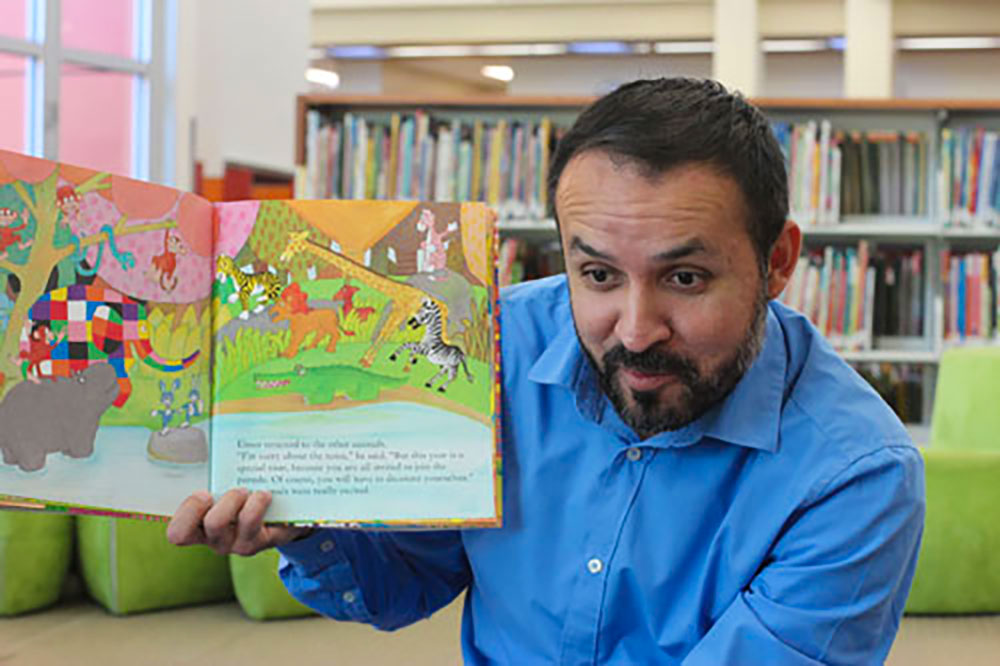 Man reading book to children