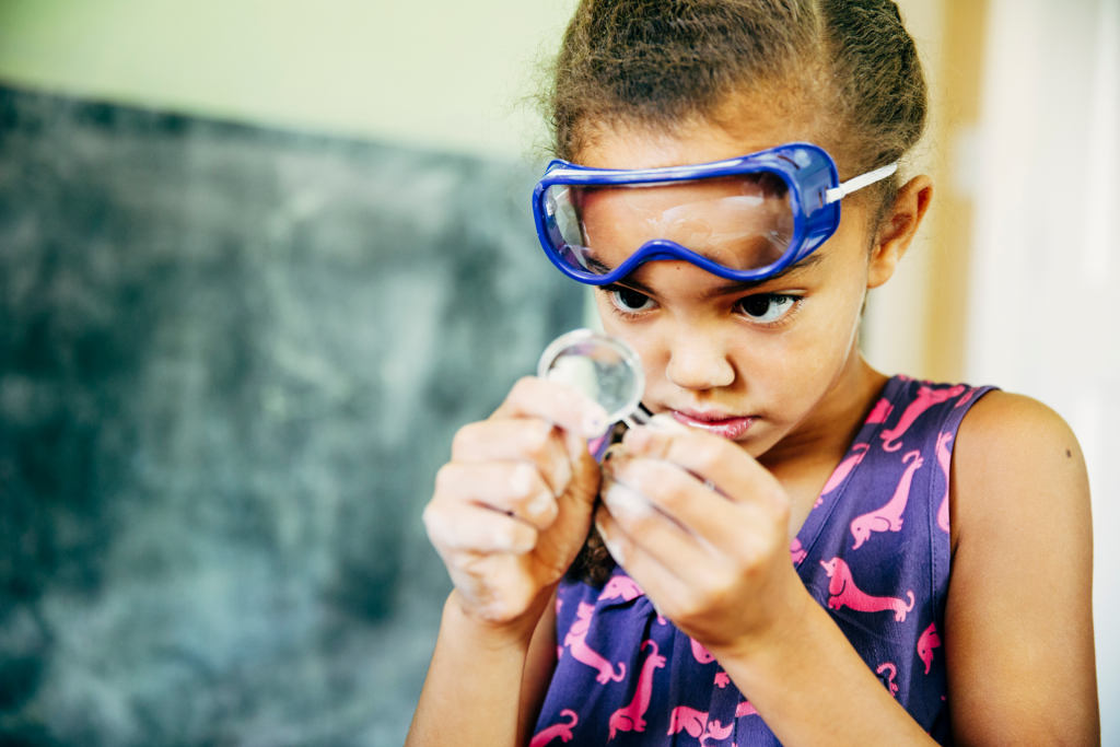 Young girl with goggles looking through magnifying glass