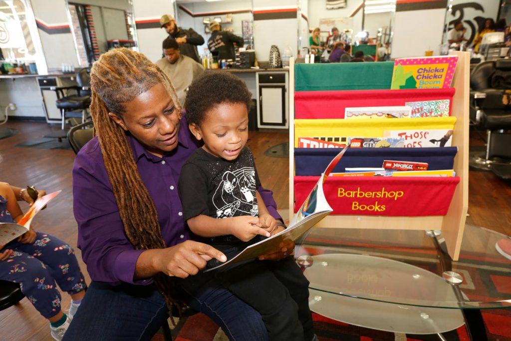 reading to child in barbershop