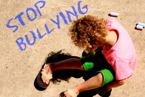 Sad child on ground with Stop Bullying written in chalk