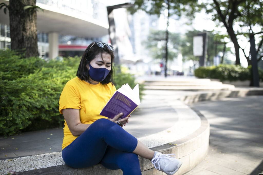 Asian female reading a book on the sidewalk