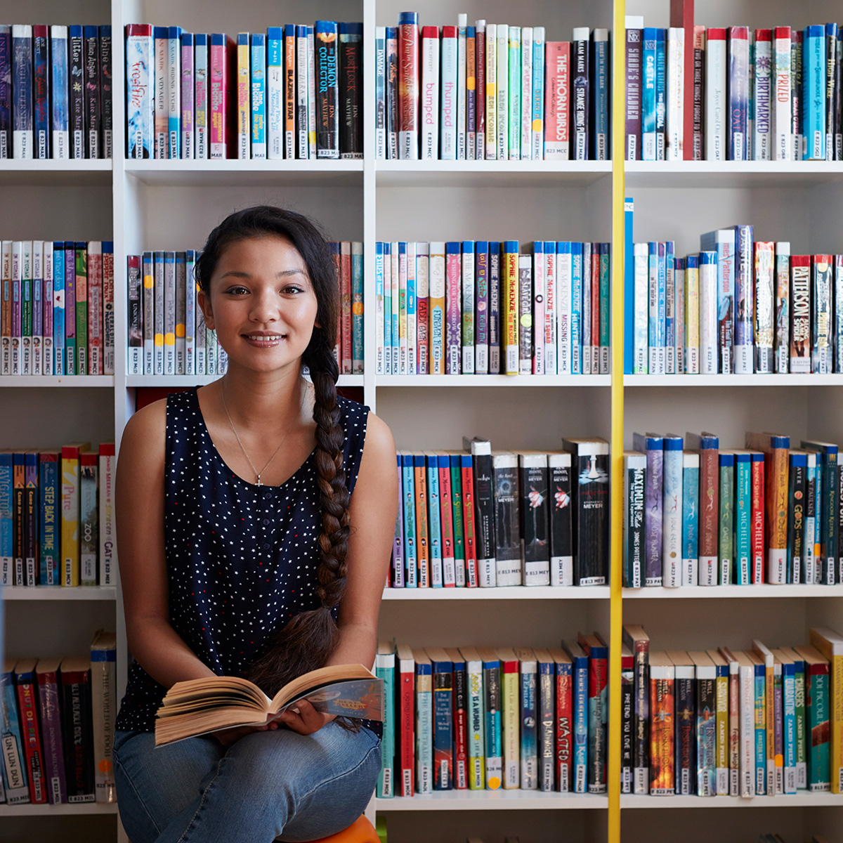 teen reading in front of bookshelf